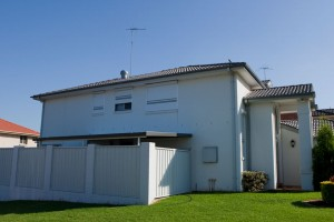 house with white home roller shutters side view