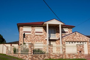 double storey brick home with gate and blockout roller shutters