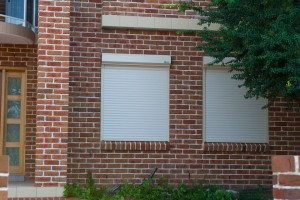 white blockout roller shutters against red brick wall