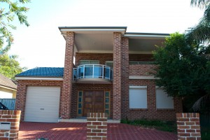 full view of two storey red brick house with garage and blockout roller shutters installed