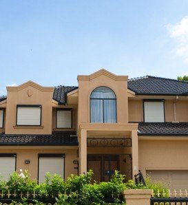 double storey beige house with dormers and bulletproof blockout shutters front view