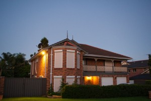 two storey red brick house with white blockout roller shutters 3/4 view