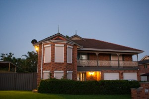 two storey red brick house with white blockout roller shutters and garden hedge