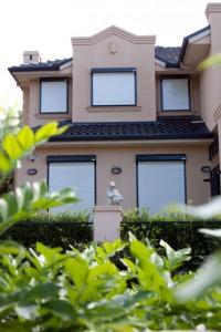 house with bulletproof window roller shutters seen from garden