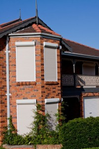 closer view of front extension of red brick house with white security roller shutters