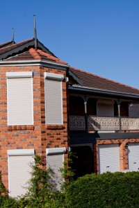 red brick house with white security roller shutters 3/4 view