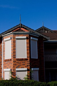 close-up of front extension of red brick house with white security roller shutters