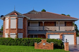 house with lacework balcony with white security roller shutters installed