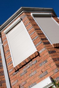 white security roller shutters on windows for red brick house