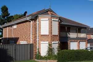 front extension of red brick house with white security roller shutters